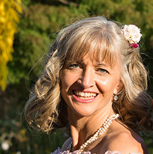 Kundin von Coiffeur Kopfarbeit mit Hochzeitsfrisur - Locken mit Echtblumen-Gesteck