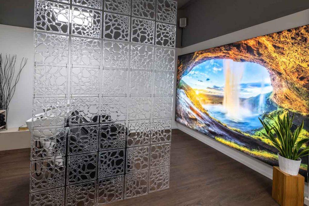 Haar-Waschbereich mit hinterleuchtetem Wandbild einer Hoehle, Wasserfall und Sonnenlicht